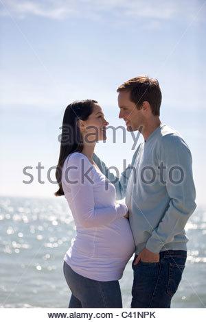 Une femme enceinte et son partenaire embrassant sur la plage Banque D'Images