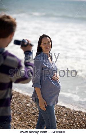 Un jeune homme prend sa partenaire enceinte sur la plage Banque D'Images