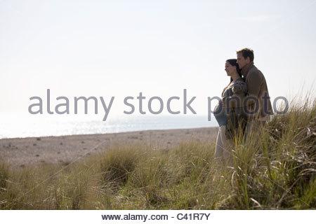 Une femme enceinte et son partenaire debout, regardant la mer Banque D'Images