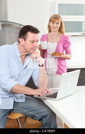Homme assis à l'aide d'un ordinateur portable à la maison, la femme tenant une tasse de thé à la recherche de café.sur. Banque D'Images