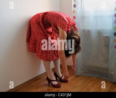 Jeune femme portant robe à pois penché au-dessus de Banque D'Images