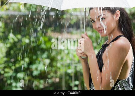 Beautiful Hispanic woman holding umbrella sous la pluie Banque D'Images