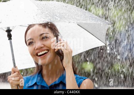 Beautiful Hispanic woman holding umbrella sous la pluie, talking on a cell phone Banque D'Images