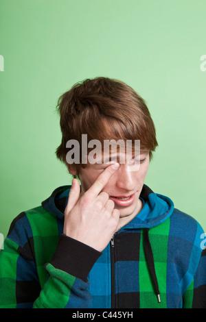 Un adolescent se frotter l'œil avec son doigt, portrait, studio shot Banque D'Images