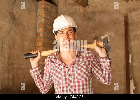 Un travailleur de la construction titulaire d'un marteau Banque D'Images