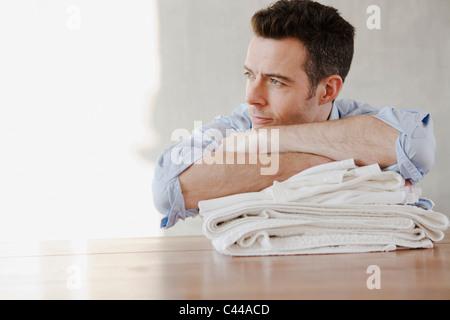Un homme se reposant sur une pile de linge plié, rêver Banque D'Images