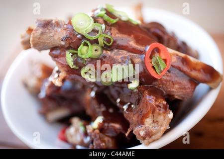 Un plat gastronomique de style chinois de porc servi avec le piment, le gingembre et oignons de printemps Banque D'Images