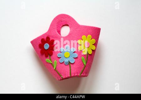 Sac feutre rose childs avec trois marguerites colorées sur il isolé sur fond blanc - prêt pour Pâques Banque D'Images