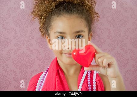Jeune fille tenant un cœur dans une chambre rose Banque D'Images