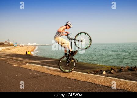 Jeune homme faisant wheelie astuces sur son vélo BMX stunts Banque D'Images