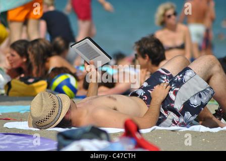 La lecture de l'homme avec un Kindle sur une plage en Italie Banque D'Images