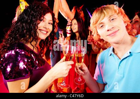 Portrait of happy couple toasting at party sur fond de joyful friends having fun Banque D'Images