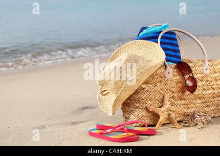 Sac de plage en été avec chapeau de paille,lunettes de soleil,une serviette et des tongs sur la plage de sable Banque D'Images