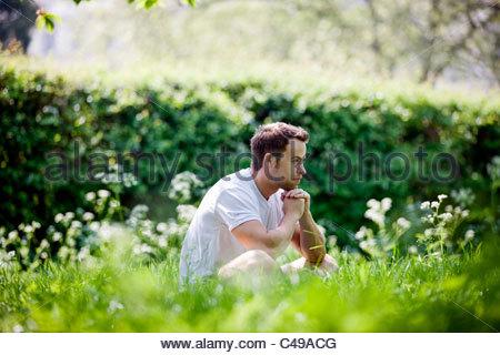 Un jeune homme assis sur l'herbe, pensant Banque D'Images