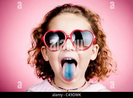 Une jeune fille aux cheveux bouclés sur un mur de studio rose portant des lunettes de soleil en forme de cœur et Banque D'Images