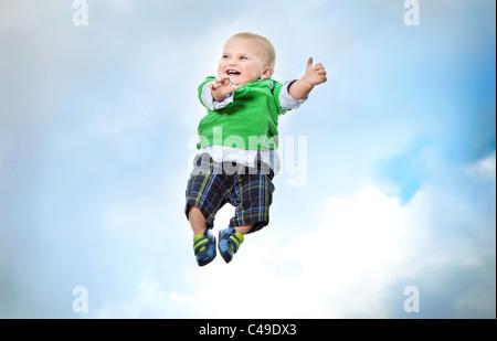 Un petit garçon dans des vêtements volant dans les airs contre un ciel bleu. Banque D'Images