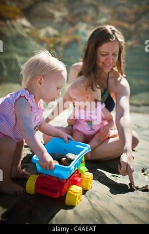 Mère jouant avec un ans filles jumeau identique à la plage Banque D'Images