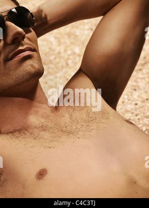 L'homme torse nu en train de bronzer sur une plage Banque D'Images