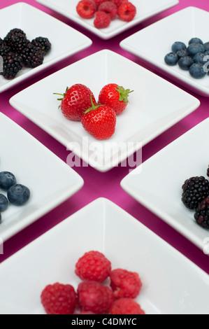 Fraises, framboises, bleuets et mûres dans des plats carrés sur fond rose Banque D'Images