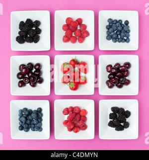 Fraises, framboises, bleuets, cerises et mûres dans des plats carrés sur fond rose Banque D'Images