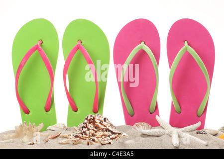Tongs dans le sable avec des coquillages. Été sur beach concept. Banque D'Images
