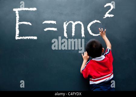 Boy drawing E=mc2 sur le mur Banque D'Images