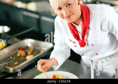 Femme chef dans un restaurant ou un hôtel cuisine cuisine délicieuse, elle termine la vaisselle Banque D'Images
