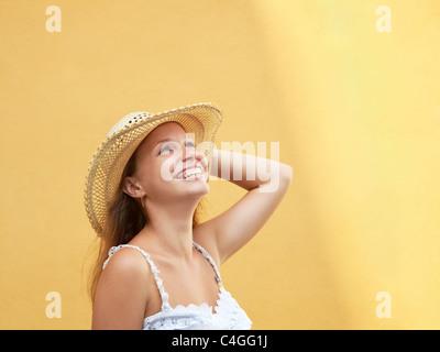 Les jeunes adultes blonde woman in straw hat rire contre mur jaune. Vue de côté, de forme horizontale, copy space Banque D'Images