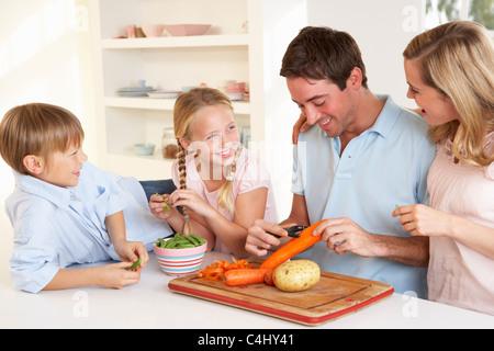 Famille heureuse peeling légumes dans la cuisine Banque D'Images