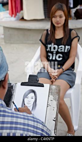 Artiste de rue, dessinant un portrait d'une jeune femme. S. E. Asie Thaïlande Banque D'Images
