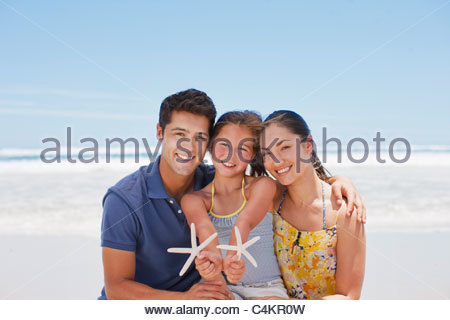 Family holding starfish on beach Banque D'Images