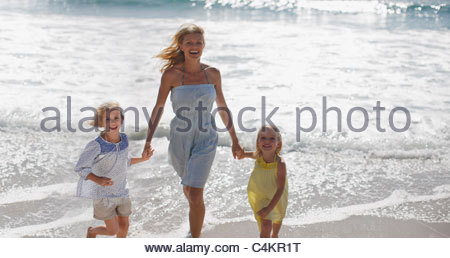 Mère et filles running on beach Banque D'Images