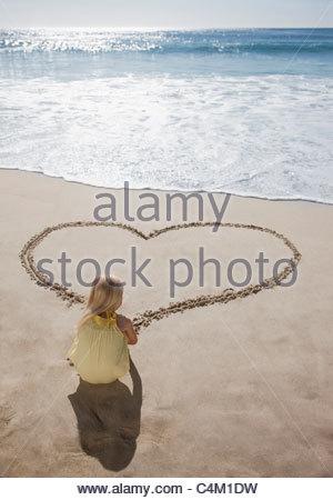 Dessin fille coeur dans le sable sur la plage Banque D'Images