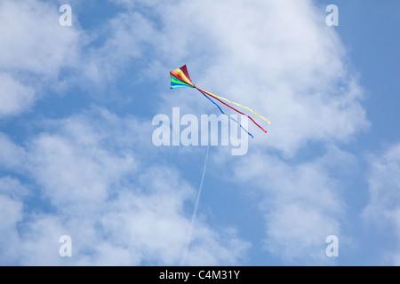 Cerf-volant arc-en-ciel sur une chaîne avec un bleu ciel nuageux, Hampshire, Angleterre, Royaume-Uni