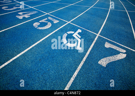 L'icône en fauteuil roulant Handicap superposée sur une piste de course. Banque D'Images