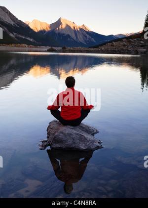 L'âge moyen man meditating on rock sur le lac Medicine, Jasper National Park, Alberta, Canada. Banque D'Images