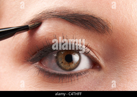 Woman applying eye make-up avec la brosse sur fond blanc Banque D'Images