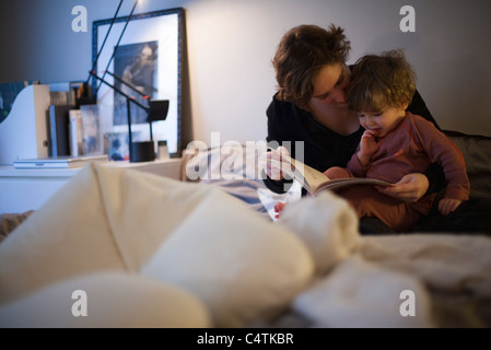 Mère tenant petit garçon sur les genoux, histoire de la lecture au lit Banque D'Images
