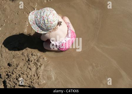 Bébé fille jouant dans le sable à la plage Banque D'Images