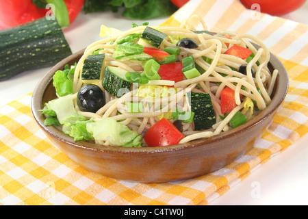 Spaghettis à la salade de laitue, poivrons, courgettes, olives, et les oignons verts sur fond blanc Banque D'Images