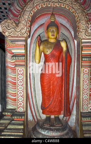 Bouddha Debout sur socle en robe rouge Triangle Culturel Grottes de Dambulla Sri Lanka Banque D'Images