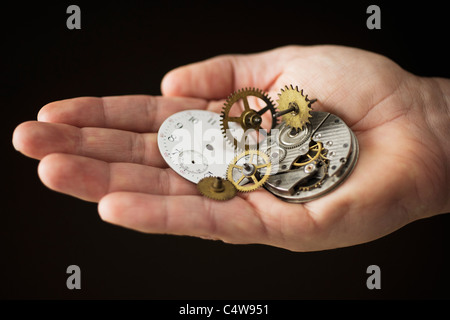 Close up of hand holding pièces d'horloge Banque D'Images