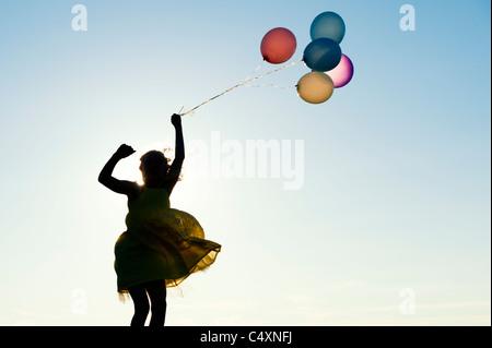 Silhouette d'une jeune fille sautant avec des ballons de couleur au coucher du soleil Banque D'Images