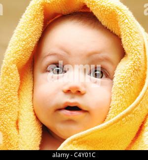 Mignon bébé visage enveloppé dans une serviette, de l'hygiène et de la santé concept Care Banque D'Images