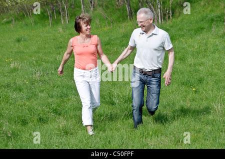 Middle-aged couple marche main dans la main dans un pré Banque D'Images