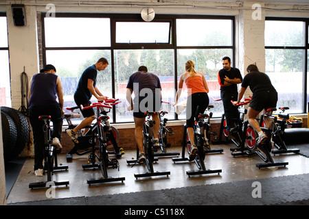 Spinning sur vélos stationnaires dans une salle de sport Banque D'Images