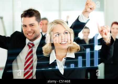 - Présentation d'affaires au sein d'une équipe; une collègue montre graphique ou diagramme d'écran Banque D'Images