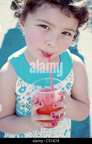 Petite fille boire du jus, portrait Banque D'Images