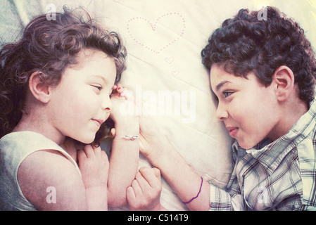 Little Boy and girl lying on bed together Banque D'Images