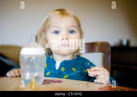 Baby Girl eating snack, portrait
